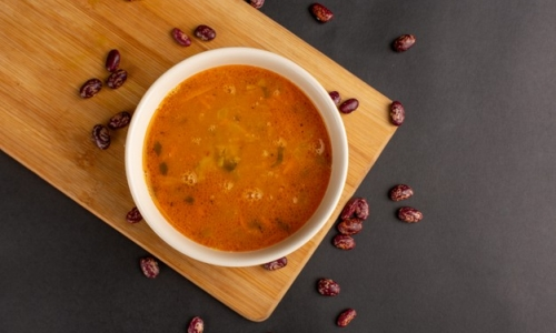 top-view-tasty-vegetable-soup-inside-plate-along-with-raw-beans-dark-surface_140725-44268